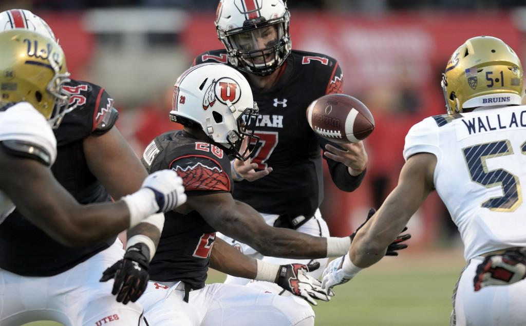 Senior quarterback Travis Wilson (7) and junior running back Joe Williams, left of Wilson, bobble the ball after the snap in the final minute of a Pac-12 football game at Rice-Eccles Stadium where the UCLA Bruins beat the Utah Utes 17-9 on Saturday, Nov. 21, 2015
