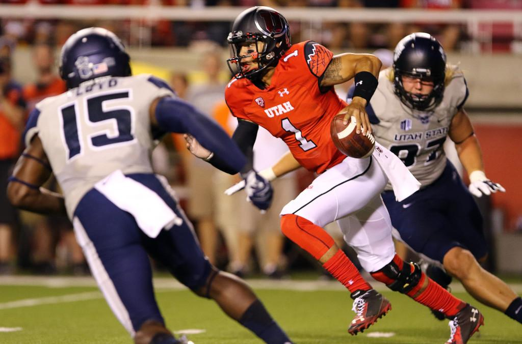 Senior quarterback Kendal Thompson (1) runs between two defenders during a football game against the Utah State Aggies at Rice Eccles Stadium, Friday, Sept. 11, 2015. Dane Goodwin, Daily Utah Chronicle.