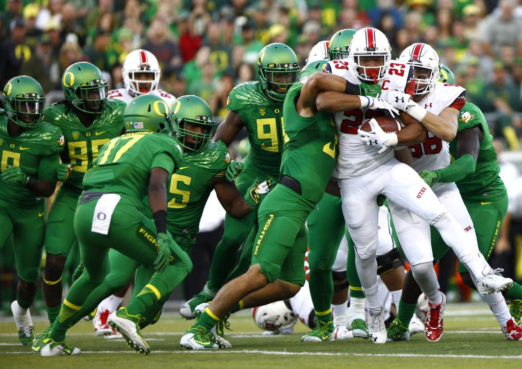 Senior running back Devontae Booker (23) tries to shed tacklers in a Pac-12 football game against the Oregon Ducks at Autzen Stadium in Eugene, Ore., Saturday, Sept. 26, 2015. Mike Sheehan, Daily Utah Chronicle.