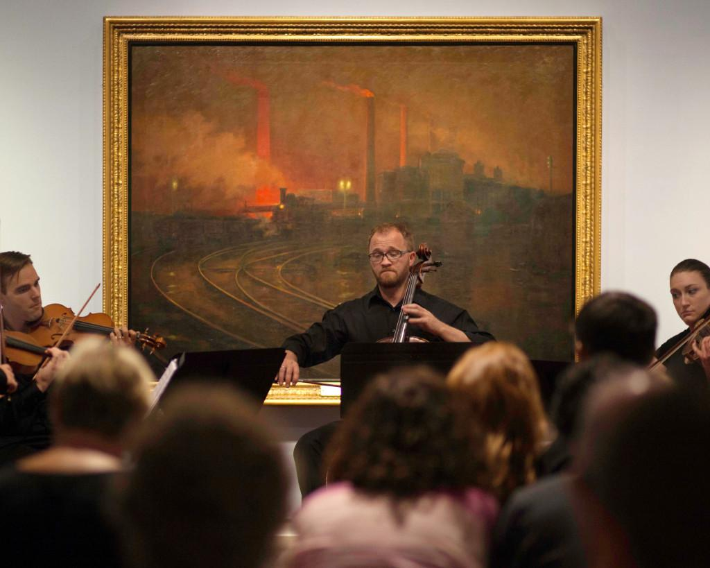 "The U graduate string quartet performs in front of Lionel Walden's ""Steelworks, Cardiff, at Night"" 1895-97, at Pastures Green & Dark Satanic Mills: The British Passion for Landscape exhibit at the Utah Museum of Fine Arts, Wednesday, September 2, 2015. Mike Sheehan, Daily Utah Chronicle."