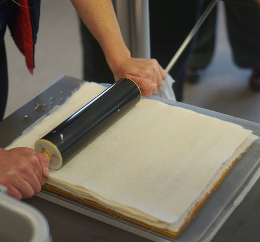 A rolling pin dries the pulp - now between two sheets of felt - that is used to create the paper at the U Book Arts Workshop on Friday, April 15, 2016. (Rishi Deka, Daily Utah Chronicle)