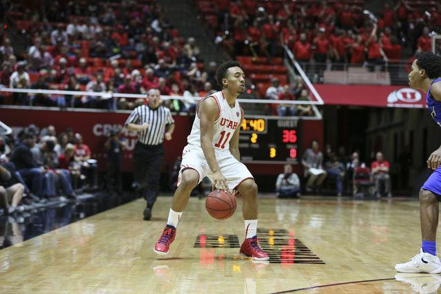 Senior guard Brandon Taylor (11) looking for the open man  in an NCAA mens basketball game against IPFW at the Jon M. Huntsman Center, Saturday, Dec 5, 2015.  Chris Ayers, The Daily Utah Chronicle.