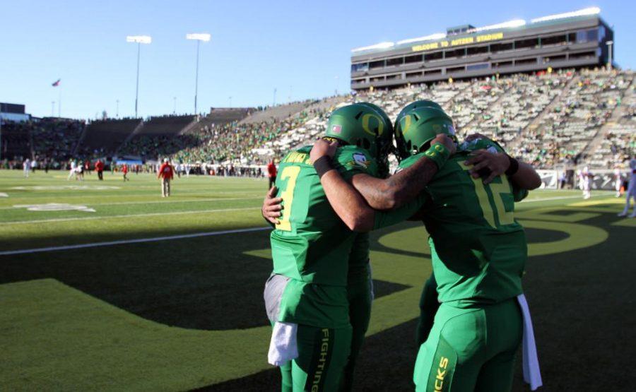 Oregon quarterbacks huddle together before playing the Utah Utes in Pac-12 action at Autzen Stadium in Eugene, Ore., Saturday, Sept. 26, 2015.
