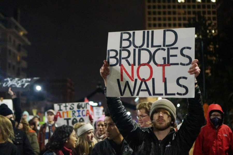 A man holds a Build Bridges Not Walls sign during President Trumps Inauguration Day protests in Salt Lake City, Utah on Friday, Jan. 20, 2017. (Rishi Deka, Daily Utah Chronicle)