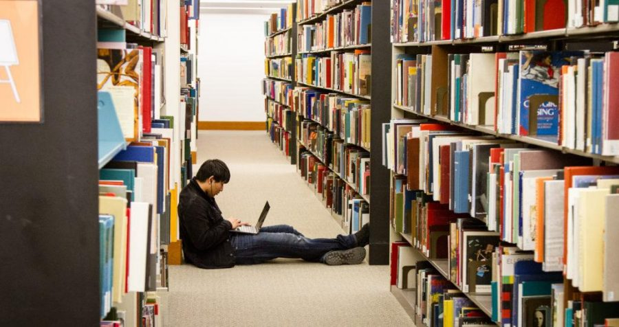Junior Hong Yang sits in the stacks at the Marriott Library and uses his laptop March 08, 2017. Adam Fondren for the Daily Utah Chronicle.