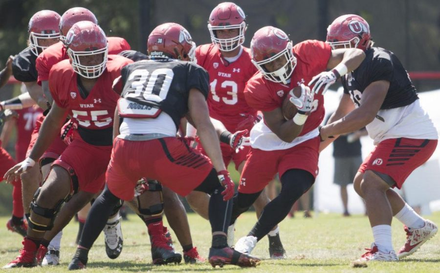 Running back Jordan Howard (26) runs through the defense during the Utah Utes football practice at Ute Baseball Field on Thursday, Aug. 10, 2017. (Rishi Deka | Daily Utah Chronicle)