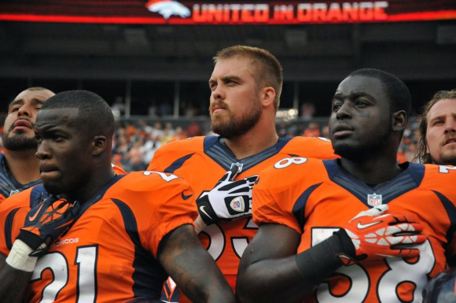 Air National Guard 1st Lt. Benjamin Garland, Denver Broncos Offensive Guard and 140th Wing Public Affairs Officer, stand with Ronnie Hillman (21) and Montee Ball (38) as he listens to the National Anthem at Sports Authority Field at Mile High Stadium, Denver, Colo. Aug 24, 2013. Garland, who originally entered the National Football League in 2010 after graduating from the U.S. Air Force Academy, was on the Bronco's reserve/military list while fulfilling his active duty obligations in the Air Force. In 2012 Garland joined the Colorado Air National Guard and made the Broncos practice squad as a defensive lineman and is competing this season to make the 53 man final roster. (Air National Guard photo by Tech. Sgt. Wolfram M. Stumpf/RELEASED)