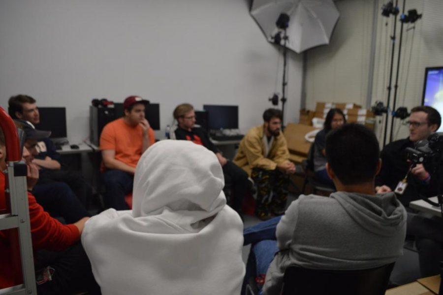 Members of Us Overwatch team watch as head coach Joe Johnson breaks down footage of their previous practice