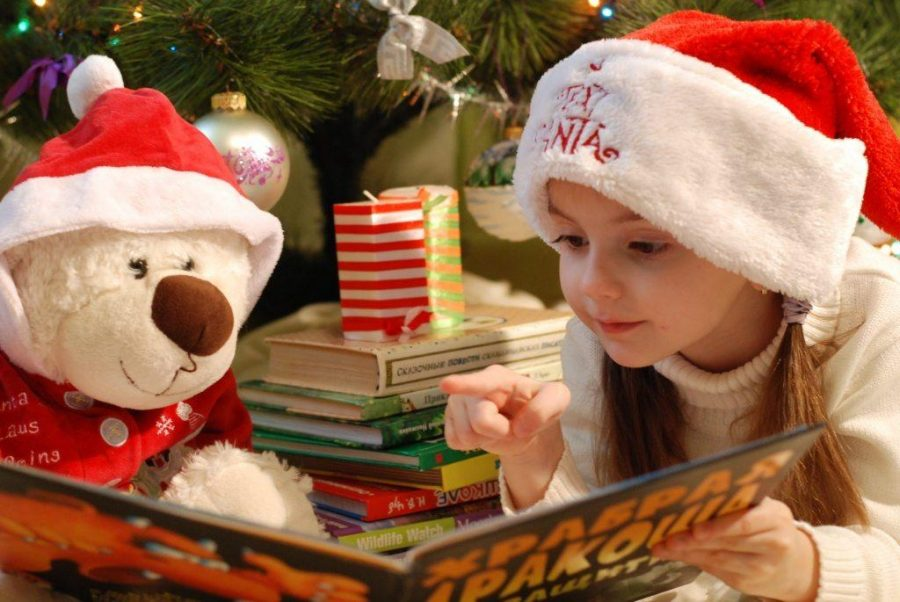 A festive little girl reads a book to her furry friend.