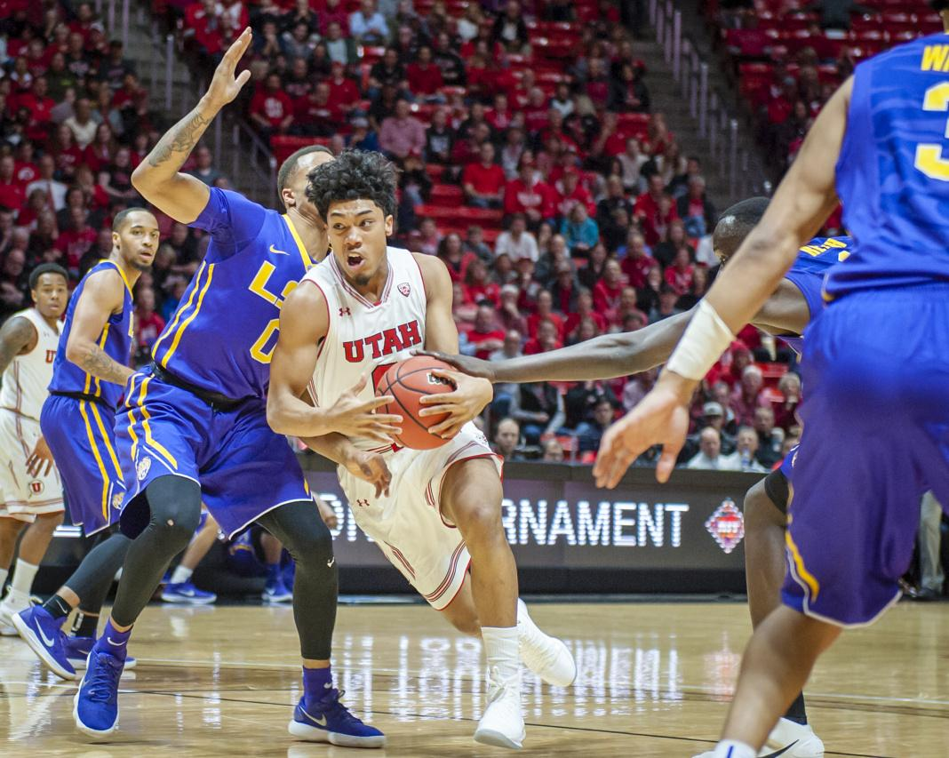 Utah Utes guard Sedrick Barefield (0) drives the lane against LSU Tigers guard Brandon Sampson (0) as the University of Utah Running Utes take on Louisiana State University Tigers in the National Invitational Tournament at the Huntsman Center in Salt Lake City, UT on Monday, March 19, 2018  (Photo by Adam Fondren | Daily Utah Chronicle)