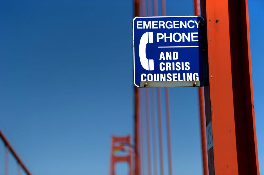Suicide prevention sign on the east sidewalk of the Golden Gate Bridge, San Francisco, California. The sign reads Emergency phone and crisis counseling.