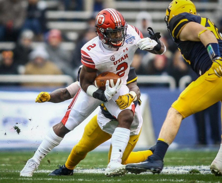 Utah Utes running back Zack Moss (2) escapes the grasp of West Virginia Mountaineers linebacker David Long Jr. (11) at the Zaxbys Heart of Dallas Bowl between the Utah Utes and the West Virginia Mountaineers in Dallas Texas on Tuesday, Dec. 26, 2017.