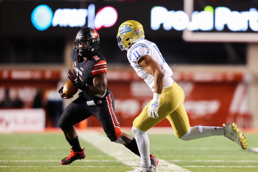 Sophomore running back Zack Moss (2) runs by a Bruin defender as the Utah Utes Football team takes on the UCLA Bruins at Rice-Eccles Stadium in Salt Lake City, UT on Friday, November 3, 2017.   (Photo by Curtis Lin/Daily Utah Chronicle)