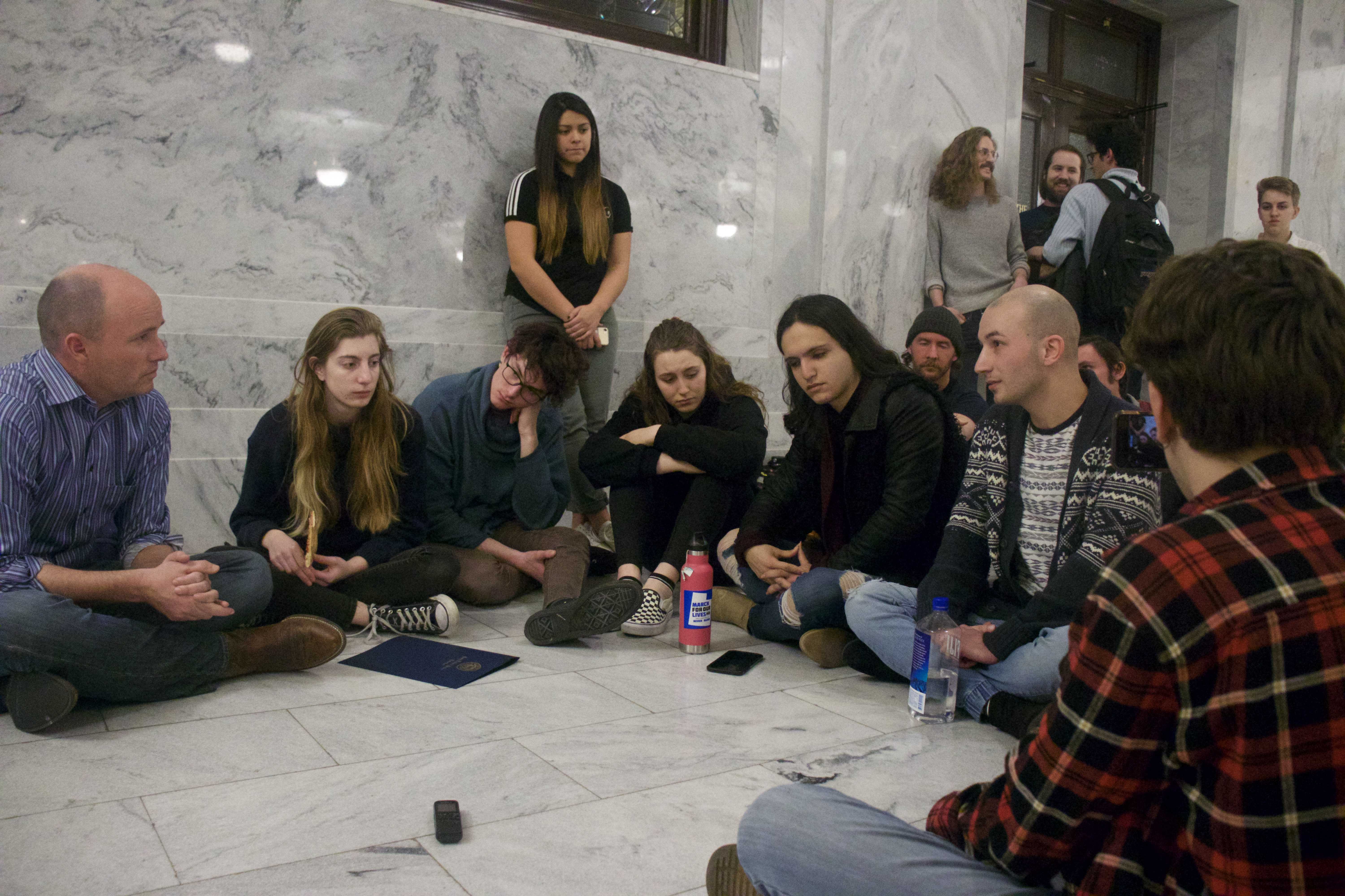 Lieutenant Gov. Spencer Cox sits with LGBTQ youth protesting conversion therapy outside of the governor's offices at the Utah Capitol.