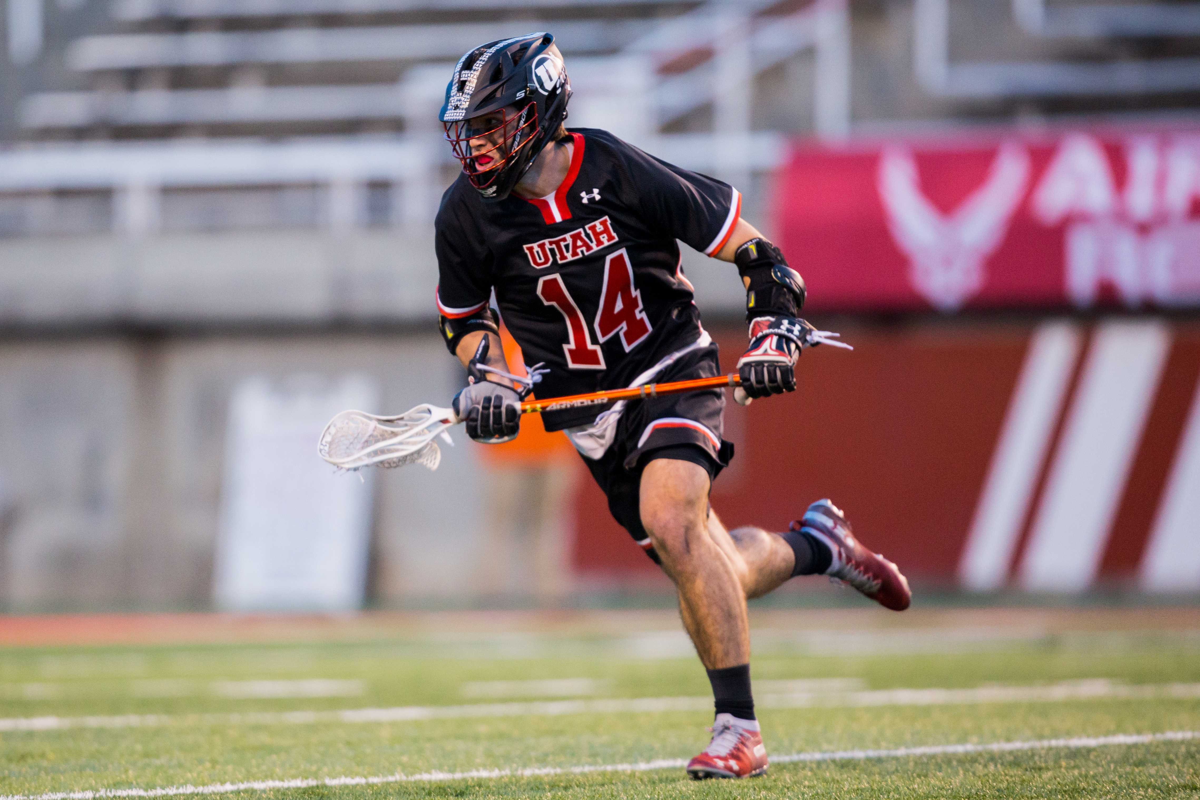 University of Utah freshman midfielder Liam Cavanaugh-Fernandez (14) looked to pass to a teammate in an NCAA Men's Lacrosse game vs. Vermont at Rice-Eccles Stadium in Salt Lake City, UT on Friday February 01, 2019.  (Photo by Curtis Lin | Daily Utah Chronicle)