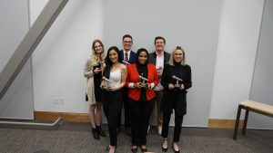 HIP Talks winners pose in the Hinckley Forum room from left to right: runners-up Avery Druton, Miranda Stewart, Zac Ray, audience favorite Isha Shadale, runner-up Bryce Wilson, and grand-prize winner Rachel Carlson. (Courtesy of the Hinckley Institute)