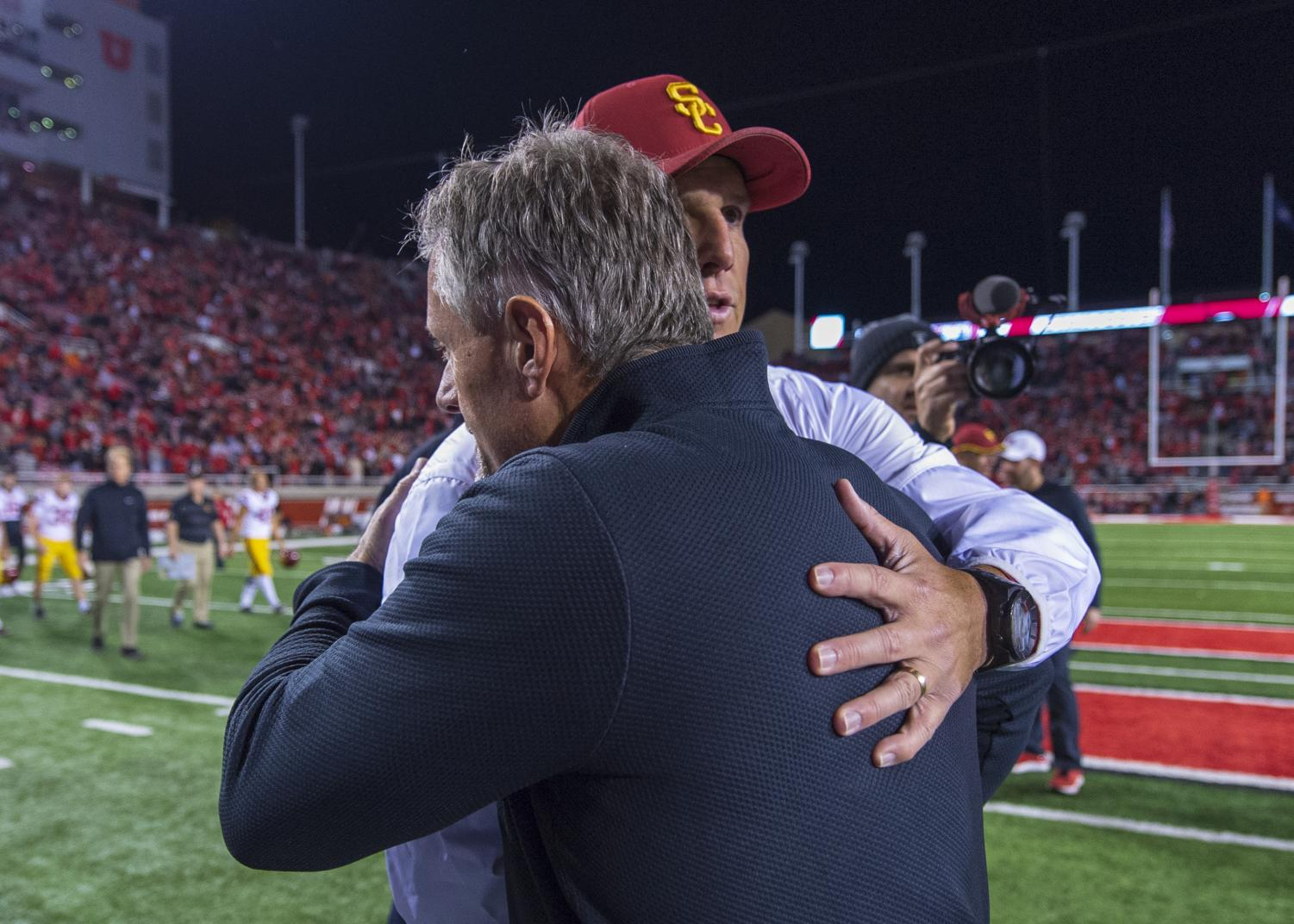 University of Utah football head coach Kyle Whittingham embraces University of Southern California football head coach Clay Helton following an NCAA Football game at Rice Eccles Stadium in Salt Lake City, Utah on Saturday, Oct. 20, 2018. (Photo by Kiffer Creveling | The Daily Utah Chronicle)