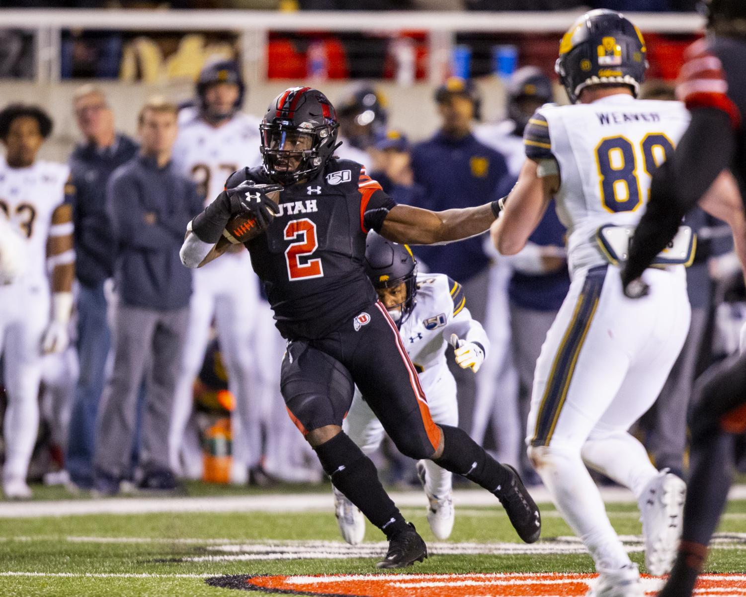 University of Utah senior running back Zack Moss (2) runs with the ball after taking a handoff from University of Utah senior quarterback Tyler Huntley (1) in an NCAA Football game vs. University of California at Rice-Eccles Stadium in Salt Lake City, UT on Saturday October 26, 2019.(Photo by Curtis Lin | Daily Utah Chronicle)