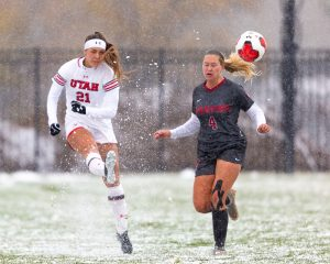 University of Utah Utes Women's soccer team forward Ireland Dunn (21) kicks the ball in a snowy field during an NCAA soccer match vs. the Stanford Cardinal women's soccer team at the Ute Soccer Field in Salt Lake City, Utah on Sunday, Oct. 27, 2019 (Photo by Abu Asib | The Daily Utah Chronicle)
