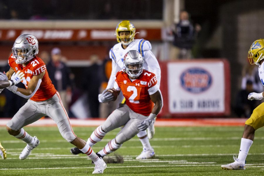 University of Utah senior running back Zack Moss (2) rushes with the ball after taking a handoff from University of Utah senior quarterback Tyler Huntley (1) in an NCAA Football game vs. UCLA at Rice-Eccles Stadium in Salt Lake City, UT on Saturday November 16, 2019.(Photo by Curtis Lin | Daily Utah Chronicle)