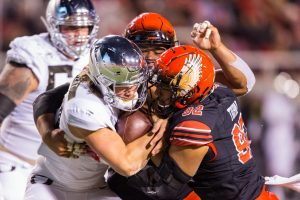 University of Utah junior defensive tackle Leki Fotu (99) and sophomore defensive end Maxs Tupai (92) tackled University of Oregon junior quarterback Justin Herbert (10) during an NCAA Football game vs. the University of Oregon at Rice-Eccles Stadium in Salt Lake City, UT on Saturday, Nov. 10, 2018.(Photo by Curtis Lin | Daily Utah Chronicle)