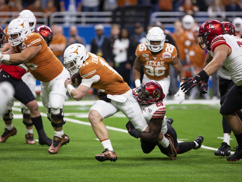 University of Utah sophomore linebacker Devin Lloyd (20) wraps up Texas QB Sam Ehlinger (11) in the Alamo Bowl against the University of Texas Longhorns on Dec. 31, 2019. (Justin Prather   Daily Utah Chronicle)