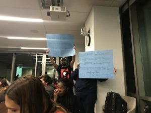 """Students hold up signs saying """"no more cops"""
