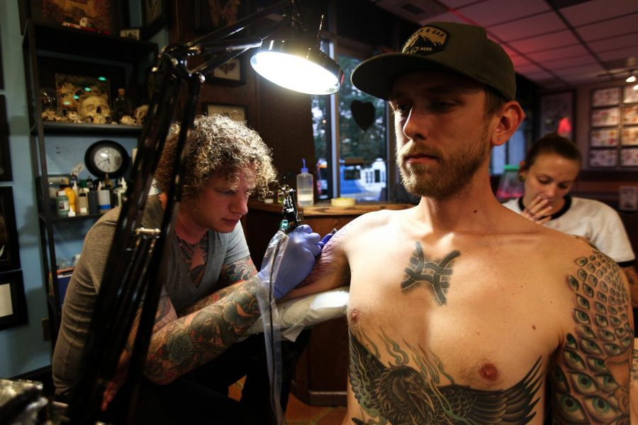 Artist Craig Secrest tattoos his customer Connor at Heart of Gold Tattoo shop in Salt Lake City. (Photo by Justin Prather | The Daily Utah Chronicle).