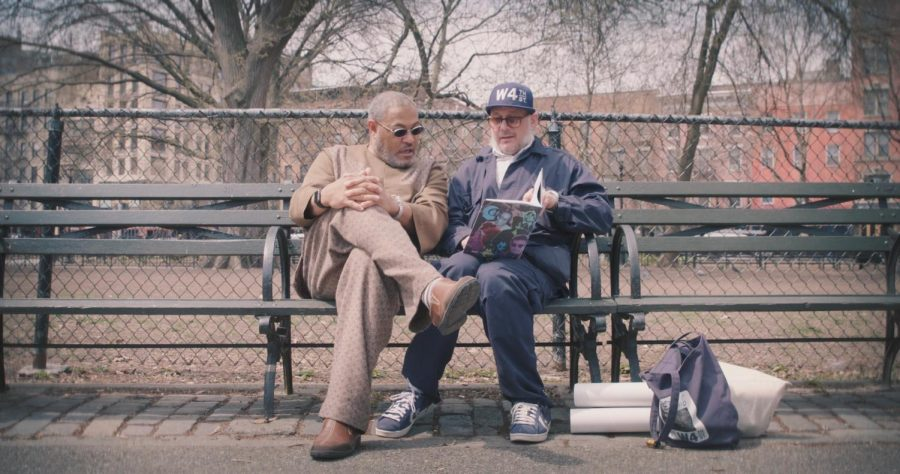 Ricky Powell and Laurence Fishburne look at a photobook together on a park bench in New York City. (Photo by Jasper Cicero | Courtesy Tribeca Enterprises)