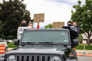 Right, Alumni Xenia Maritsa, Natalie Griswold, Jessica Arthurs and Tara Arthurs sit on their jeep while listening to speaker at the caravan protest in Salt Lake City on June 6, 2020.