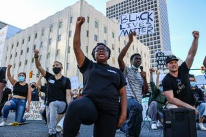 Grace Cunningham and Ammon Roberts take a knee with fellow protestors after marching from the state capitol to the Wallace Bennett Federal Building in solidarity with the Black Lives Matter movement on June 9, 2020. (Photo by Ivana Martinez   Daily Utah Chronicle)
