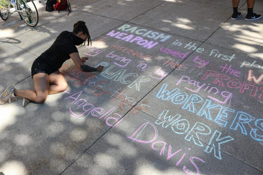 Attendee writes an Angela Davis quote in chalk at Washington Square Park for the Juneteenth celebration in Salt Lake City on June 19, 2020. (Photo by Ivana Martinez | Daily Utah Chronicle)