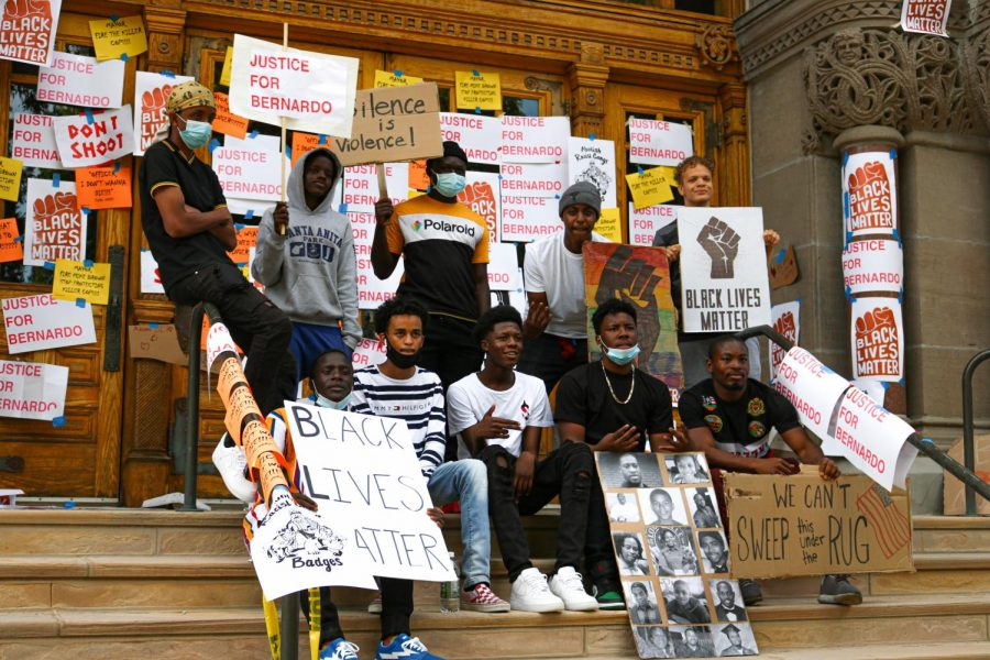 Attendees took a picture at the Washington Square park building where signs of the Black Lives Matter Movement decorated the building for Juneteenth.  (Photo by Ivana Martinez | Daily Utah Chronicle)
