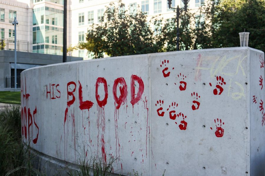 """Protesters paint the district attorney office in Salt Lake City red to illustrate the """"blood on Gills hands""""  after the earlier decision that declared officers involved in the killing of Bernardo Palacios-Carbajal as justified on July 9, 2020. (Photo by Ivana Martinez 
