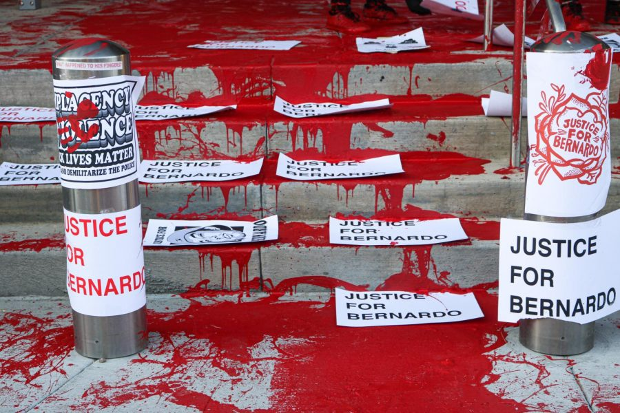 """Protesters paint the district attorney office in Salt Lake City red to illustrate the """"blood on Gill"""