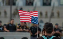 A masked demonstrator, holding an upside down American flag, faces Utah law enforcement officers gathered in front of the Utah State Capitol Building on June 4th, 2020. (Photo by Mark Draper | The Daily Utah Chronicle)