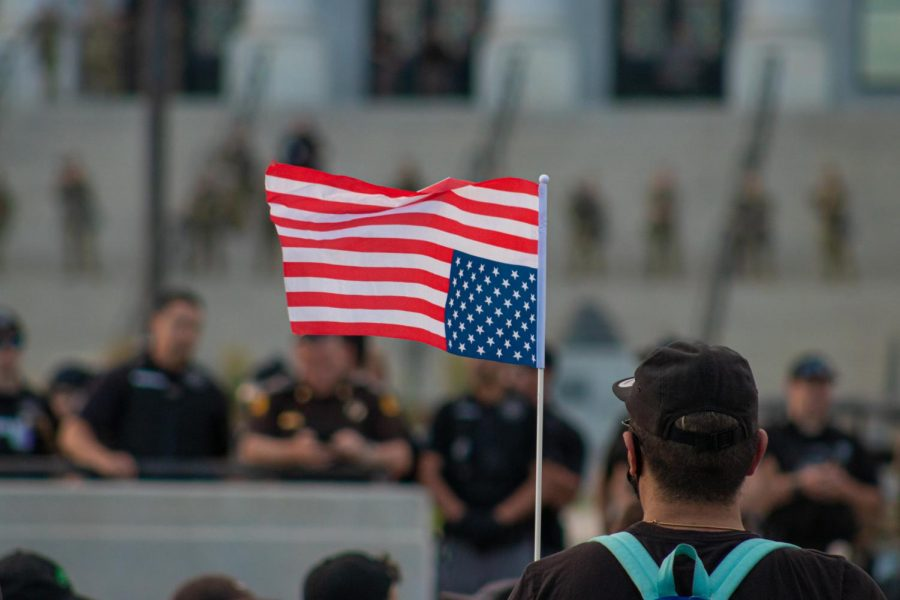 A+masked+demonstrator%2C+holding+an+upside+down+American+flag%2C+faces+Utah+law+enforcement+officers+gathered+in+front+of+the+Utah+State+Capitol+Building+on+June+4th%2C+2020.+%28Photo+by+Mark+Draper+%7C+The+Daily+Utah+Chronicle%29