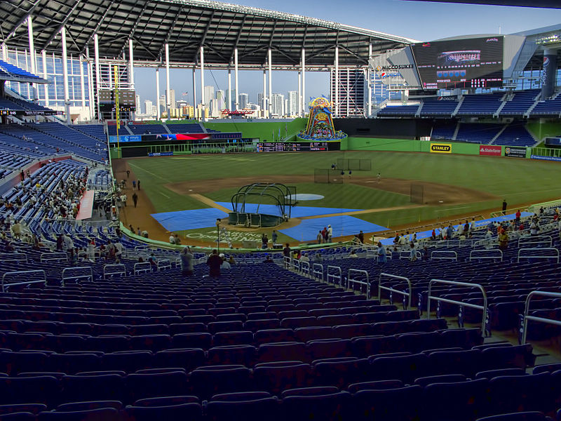 The field at Marlins Park with the Miami skyline in the background. In left centerfield is the Home Run Feature that animates should the Marlins hit a home run. The equipment on the field is for a Marlins batting practice in preparation for Opening Day 2012. (Image via Wikimedia Commons)