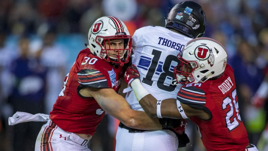 University of Utah senior linebacker Cody Barton (30) and Javelin K. Guidry (28) tackle Northwestern University senior quarterback Clayton Thorson (18) during the San Diego County Credit Union Holiday Bowl at SDCCU Stadium in San Diego, California on Monday, Dec. 31, 2018. (Photo by Kiffer Creveling | The Daily Utah Chronicle)