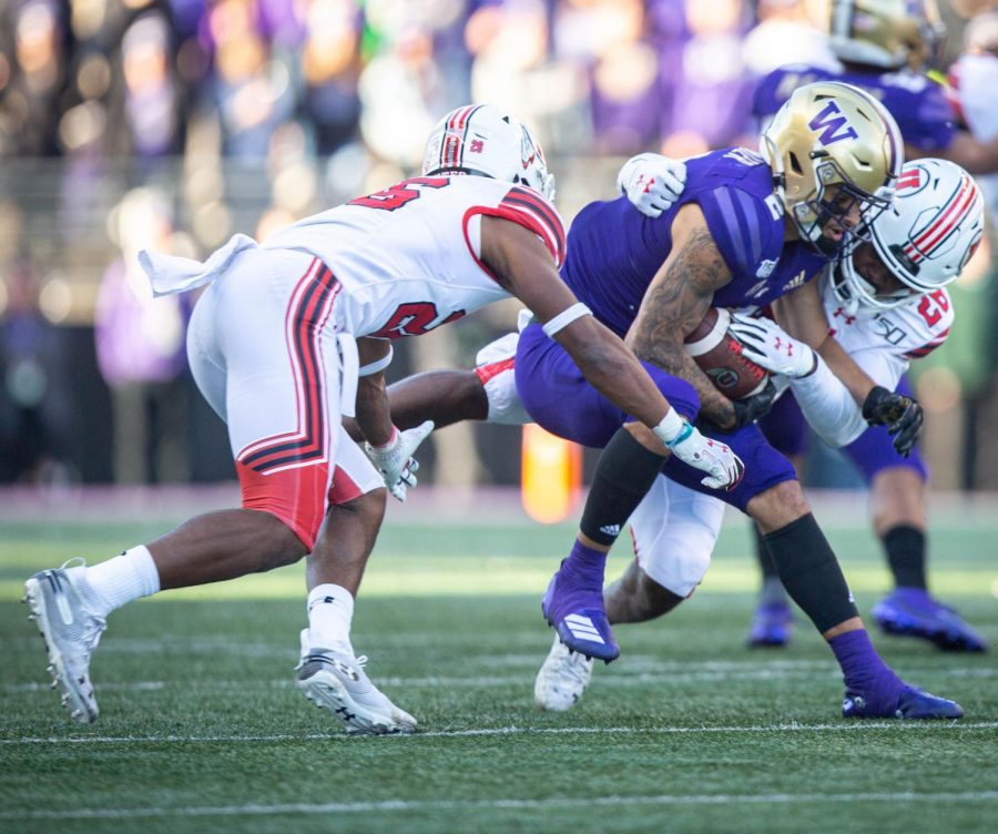 University of Utah defense tackling Washinton wide reciever Aaron Fuller (2) in an NCAA Football game vs. The Washington Husky in Husky Stadium in Seattle, Washington on Saturday, Nov. 2, 2019(Photo by Cassandra Palor | The Daily Utah Chronicle)