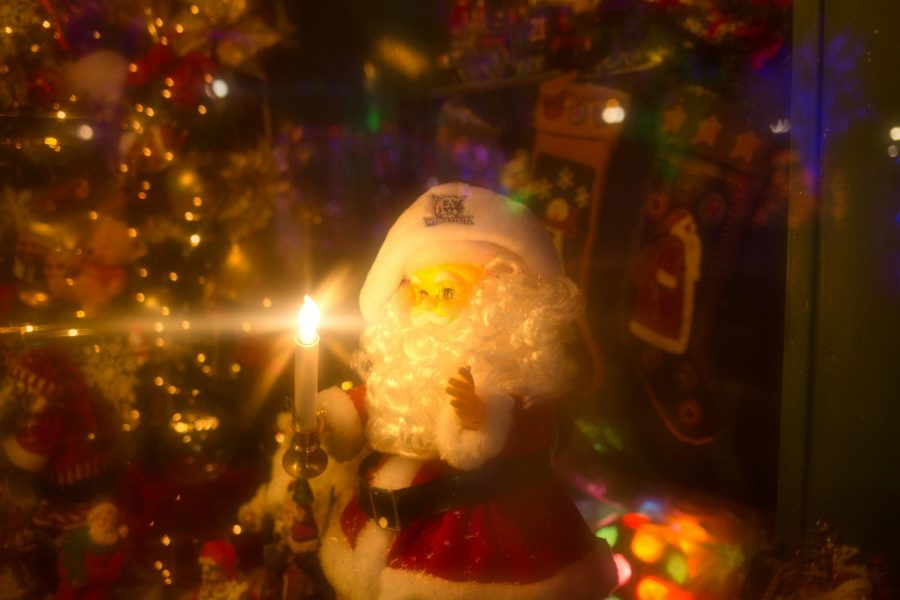 A miniature Santa Claus holds a candle inside a showcase at the Ogden Christmas Village during Thanksgiving on Nov. 28, 2018 (Photo by Abu Asib | The Daily Utah Chronicle)