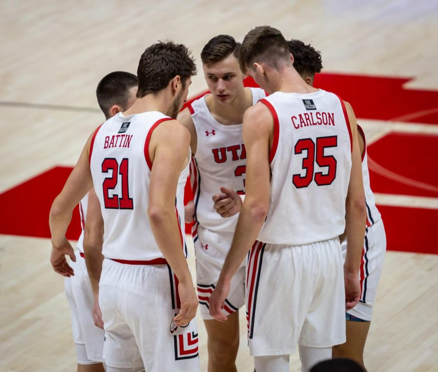 University of Utah Men's Basketball players Rylan Jones (#15), Timmy Allen (#1), Pelle Larsson (#3), Riley Battin (#21), and Branden Carlson (#35) discuss their game plan in the season-opening game against the University of Washington in the Jon M. Huntsman Center on U of U campus on Dec. 3, 2020. (Photo by Jack Gambassi | The Daily Utah Chronicle)