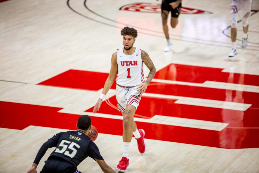 University of Utah Men's Basketball guard Timmy Allen (#1) looks for a pass through the University of Washington defense in the opening game between the two teams in the Jon M. Huntsman Center on U of U campus on Dec. 3, 2020. (Photo by Jack Gambassi | The Daily Utah Chronicle)