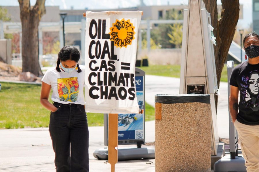 Zahra Saifee holds a sign at a climate protest held by Divest U at the Union Plaza on April 22, 2021. (Photo by Natalie Colby   Daily Utah Chronicle)