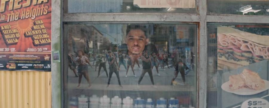 Usnavi (Anthony Ramos) looks through his bodegas window to watch Washington Heights residents dancing in the street.(Courtesy HBO Max)