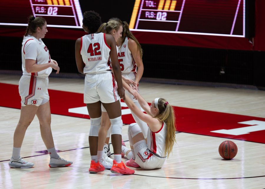 University of Utah womens basketball player, Dru Gylten (#10), is helped up by teammates, Andrea Torres (#3), Brynna Maxwell (#11), Peyton McFarland (#42), and Kemery Martin (#15), in the game against Arizona State University in the Jon M. Huntsman center in Salt Lake City on Dec. 18, 2020. (Photo by Jack Gambassi | The Daily Utah Chronicle)