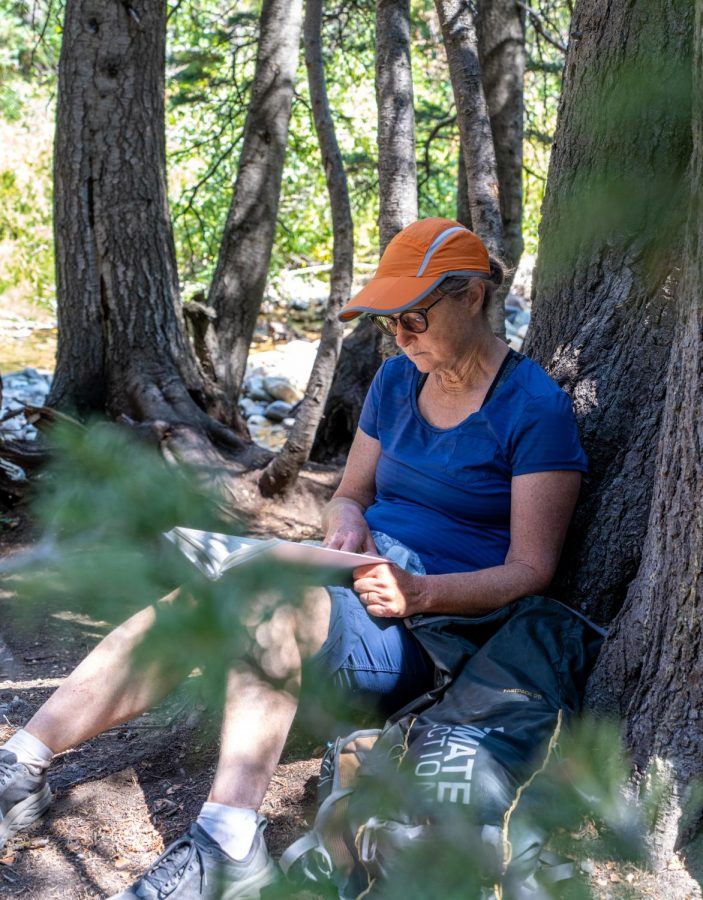 Jamie McDonald reads a book by Little Cottonwood Creek in Little Cottonwood Canyon, Utah on Sept. 5, 2021. (Photo by Xiangyao Axe Tang | The Daily Utah Chronicle)